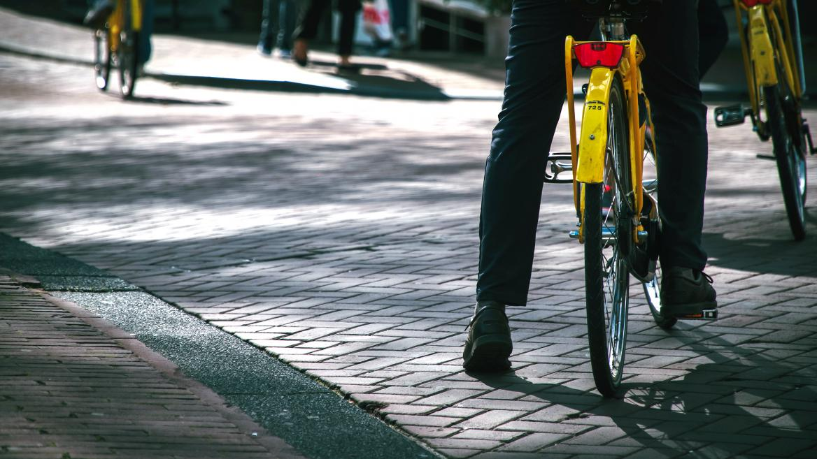 professionally dressed individual's leg touches brick pavement while pausing astride yellow community bicycle