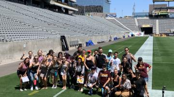 Events management students taking PRM 486 take a group shot from the field of Sun Devil Stadium